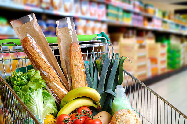 Shopping cart full of food in supermarket aisle elevated view stock photo