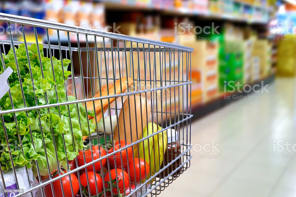 Shopping cart full of food in supermarket aisle side tilt stock photo