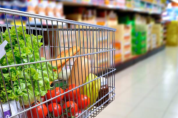 Shopping cart full of food in supermarket aisle side tilt stock photo