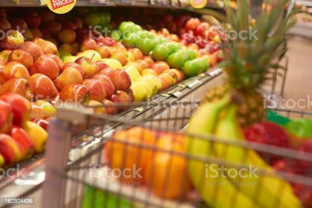 Shopping Cart Full Of Fruit Shopping Cart Full Of Fruit at the supermarket. Selective Focus, Grocery Shopping for fruit. Aisle Stock Photo