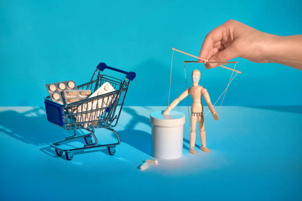 Shopping cart full of medicines - useless against flu and Covid-19 but very expensive. Depending on pharmaceuticals concept. A sinister hand controlling sick patient puppet with flu face mas stock photo