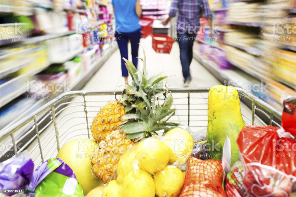 Shopping Cart Full With Groceries While Couple Walking In Front royalty-free stock photo