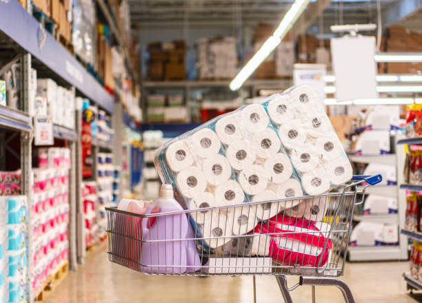 shopping cart full with products in a large supermarket - carta igienica foto e immagini stock