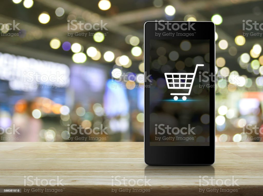 Shopping cart Icon on smart phone screen over blur mall stock photo