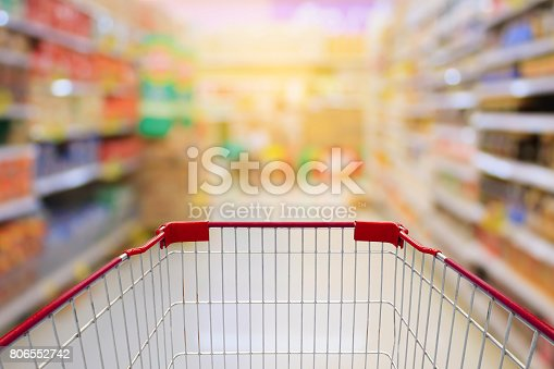 istock Shopping cart in Supermarket Aisle and Shelves in blur background 806552742