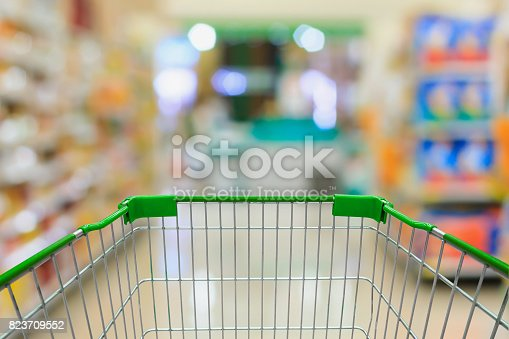 istock Shopping cart in Supermarket Aisle and Shelves in blur background 823709552