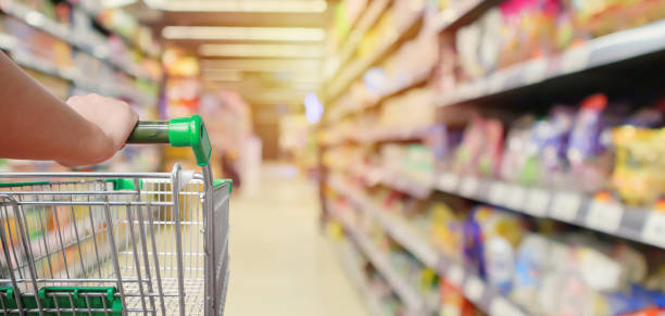 shopping cart in supermarket aisle with product shelves interior defocused blur background - shopping стоковые фото и изображения