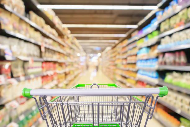 Einkaufswagen im Supermarkt-Gang mit Produktregalen Innenraum verunreinigtem Hintergrund – Foto