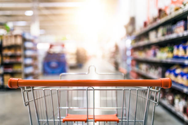 Shopping cart in supermarket Abstract blurred photo of store with trolley in department store background. Supermarket aisle with empty red shopping cart discount store stock pictures, royalty-free photos & images