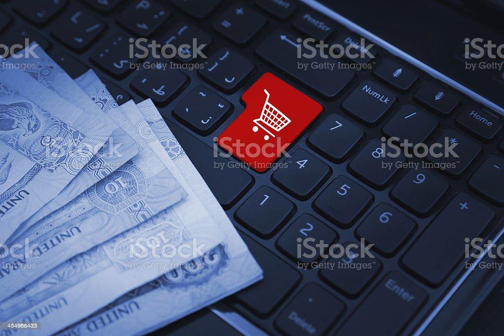 shopping cart keyboard key with dirhams bills stock photo
