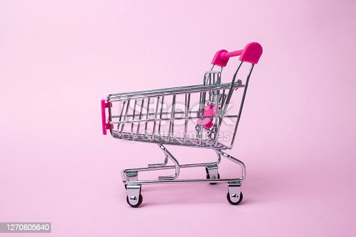 A Shopping Cart. Mini shopping trolley, on pink background. Mini Shopping Cart. Business, e-commerce conce