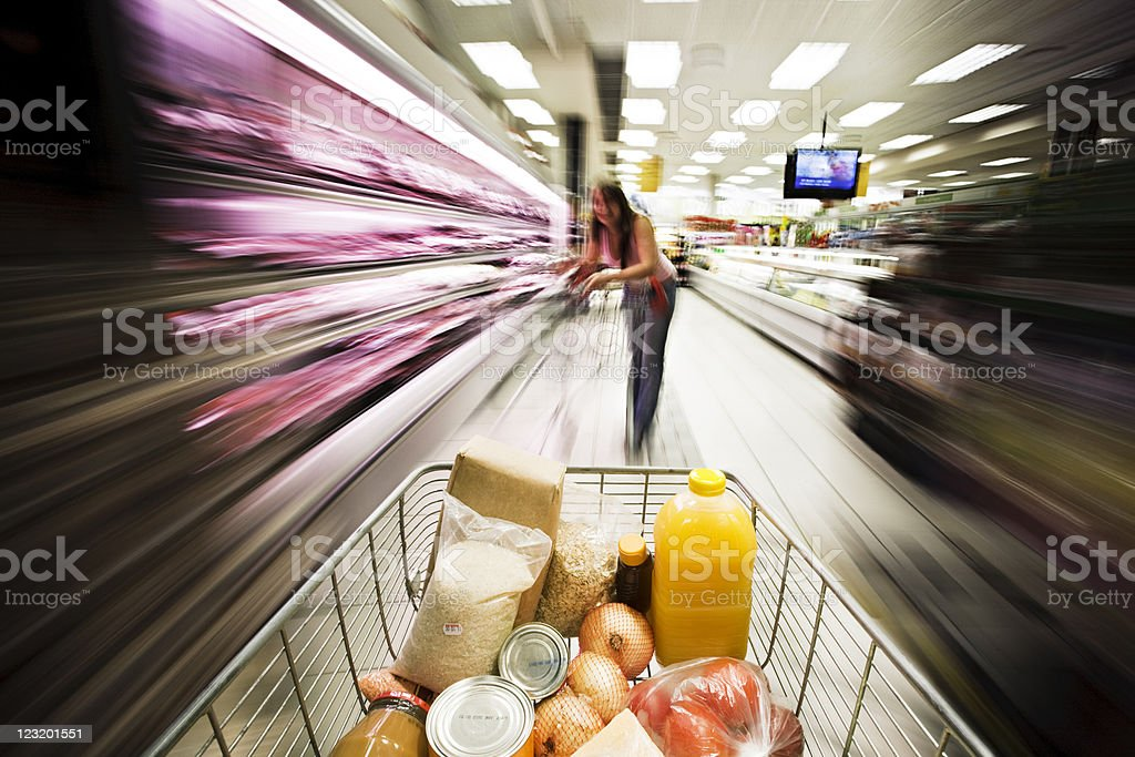 Shopping cart moves past meat cabinet. Motion blur obscures background. royalty-free stock photo