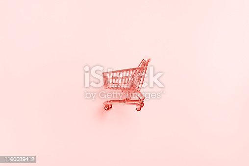 istock Shopping cart on trendy coral color background. Minimalism style. Shop trolley at supermarket. Sale, discount, shopaholism concept. Consumer society trend 1160039412
