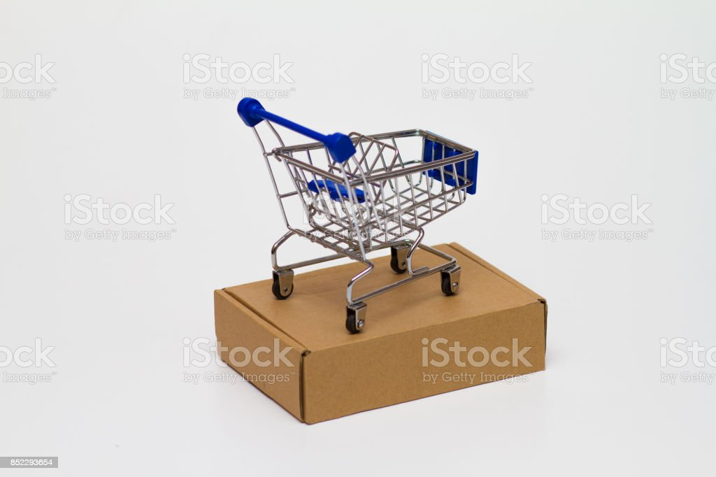 Shopping Cart over a box on white background stock photo