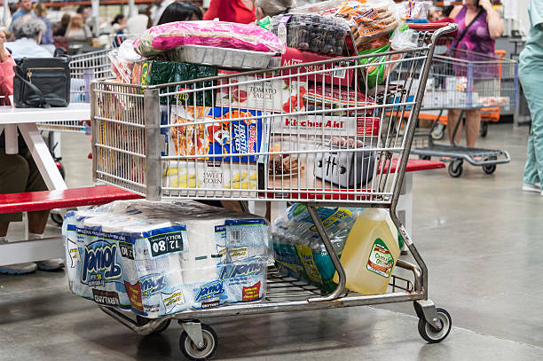 """Shopping cart """"Miami, Florida, USA- November 5, 2012: Shopping cart full of merchandise in a local macrostore. Inside the cart we can see toiled paper, corn oil,corn flakes, etc."""" full stock pictures, royalty-free photos & images"""