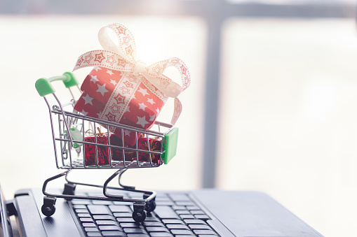 Online shopping concept. Shopping cart, small boxes and laptop