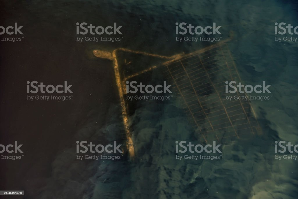 Shopping cart under water in a pond stock photo