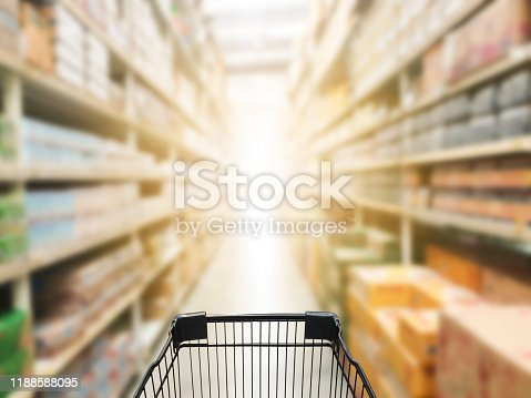 836871040 istock photo Shopping cart view in Supermarket aisle with product shelves abstract blur defocused background. 1188588095