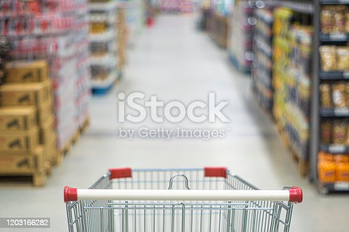 836871040 istock photo Shopping cart view in Supermarket aisle with product shelves abstract blur defocused background 1203166282