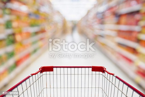 836871040 istock photo Shopping cart view in Supermarket aisle with product shelves abstract blur defocused background 835798356