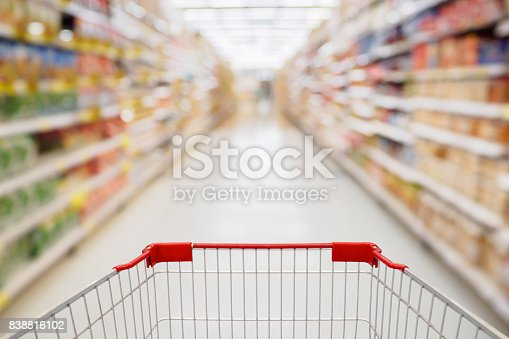836871040 istock photo Shopping cart view in Supermarket aisle with product shelves abstract blur defocused background 838816102