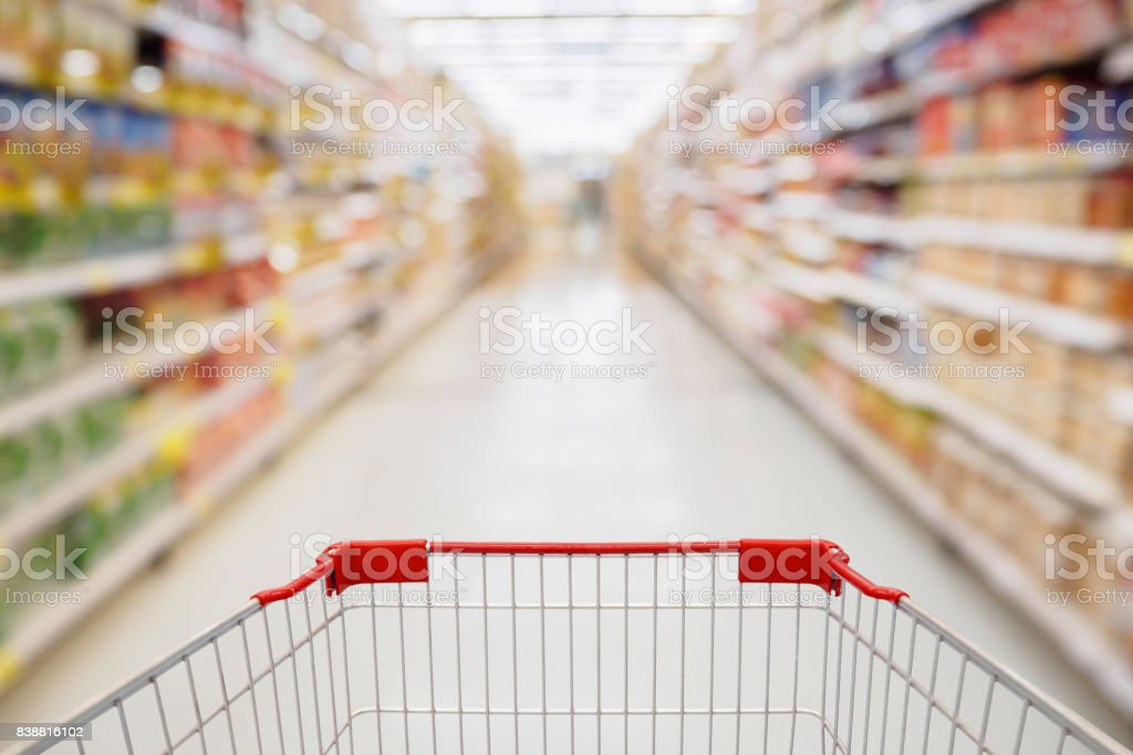 Shopping cart view in Supermarket aisle with product shelves abstract blur defocused background stock photo