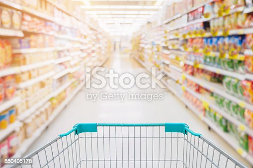 836871040 istock photo Shopping cart view in Supermarket aisle with product shelves abstract blur defocused background 850405178