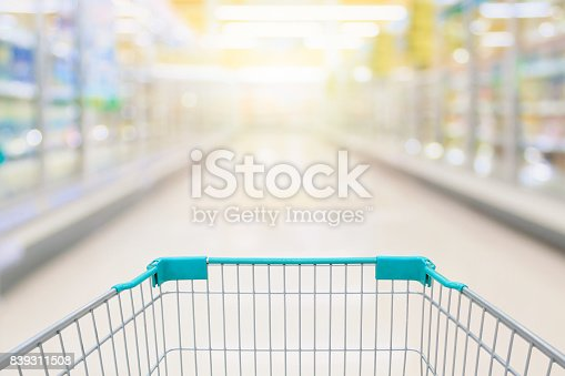 istock Shopping cart view with milk and yogurt product shelves aisle in supermarket 839311508