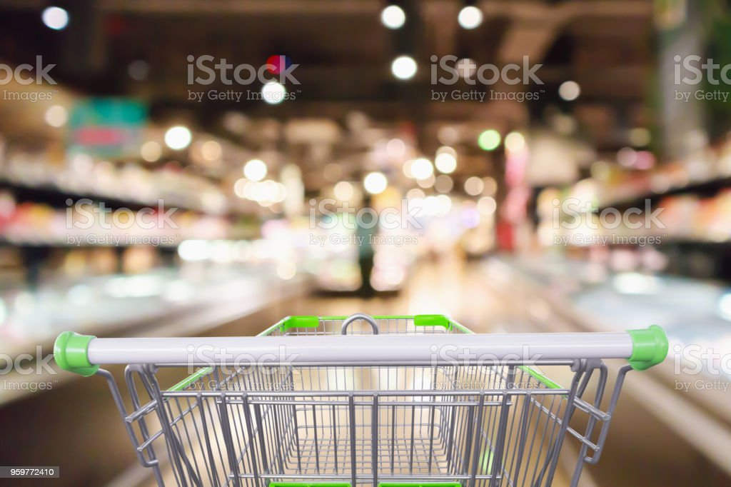 shopping cart with Abstract supermarket grocery store refrigerator blurred defocused background with bokeh light stock photo