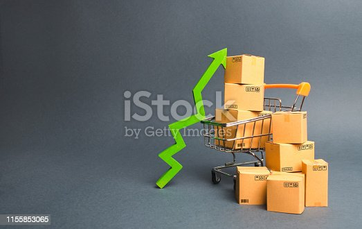 istock Shopping cart with cardboard boxes and a green up arrow. Increase the pace of sales and production of goods. Improving consumer sentiment, economic growth. Strategy for increasing revenue 1155853065