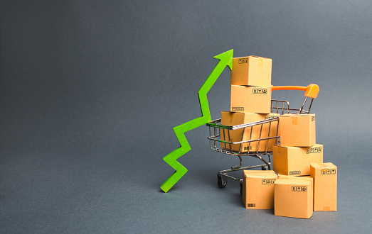 1155852718 istock photo Shopping cart with cardboard boxes and a green up arrow. Increase the pace of sales and production of goods. Improving consumer sentiment, economic growth. Strategy for increasing revenue 1155853065