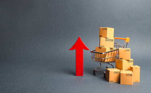 1155852718 istock photo Shopping cart with cardboard boxes and red up arrow. Growth wholesale and retail. Improving consumer sentiment, economic growth. Rising prices for goods, inflation. growth of popularity of the product 1155852718