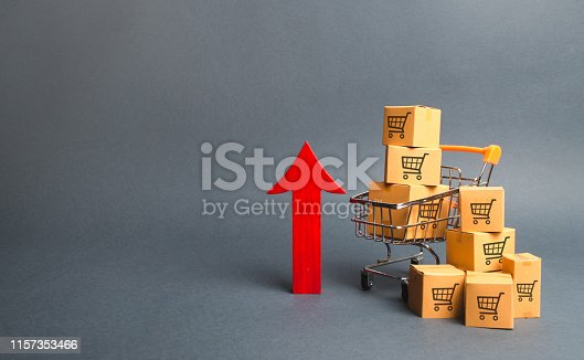 istock Shopping cart with cardboard boxes with a pattern of trading carts and a red up arrow. Growth wholesale and retail. Improving consumer sentiment, economic growth. Rising prices for goods, inflation 1157353466