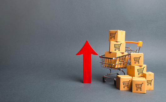 1155852718 istock photo Shopping cart with cardboard boxes with a pattern of trading carts and a red up arrow. Growth wholesale and retail. Improving consumer sentiment, economic growth. Rising prices for goods, inflation 1157353466