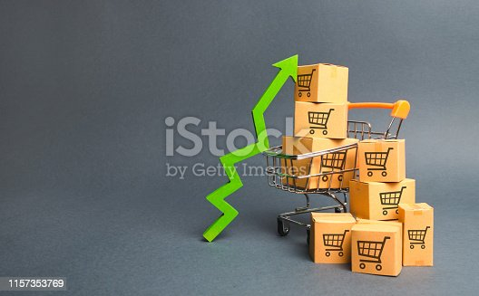 istock Shopping cart with cardboard boxes with a pattern of trading carts and a green up arrow. Increase the pace of sales, production of goods. Improving consumer sentiment. Strategy for increasing revenue 1157353769