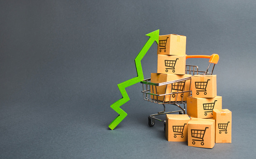 1155852718 istock photo Shopping cart with cardboard boxes with a pattern of trading carts and a green up arrow. Increase the pace of sales, production of goods. Improving consumer sentiment. Strategy for increasing revenue 1157353769
