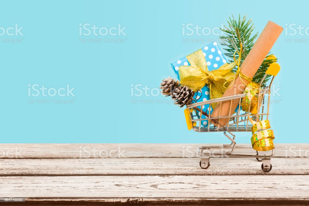 Shopping cart with christmas decoration on wood over blue background royalty-free stock photo