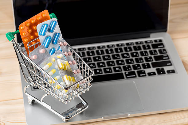 Shopping cart with different tablets on laptop keyboard stock photo