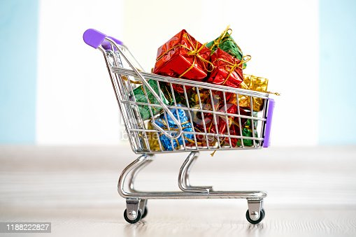 Shopping cart with presents or gift boxes. Christmas shopping concept. Trolley cart with gifts. Black Friday concept.