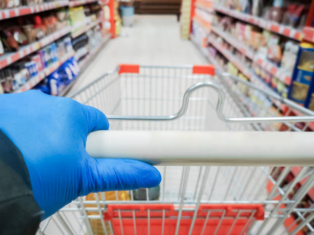 Shopping cart with protective gloves stock photo