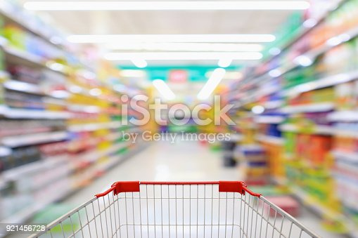 922721264 istock photo Shopping cart with supermarket aisle blur abstract background 921456728