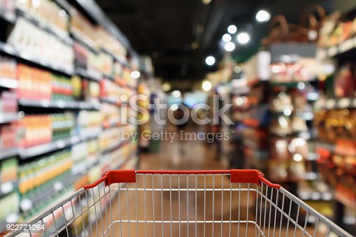 istock Shopping cart with supermarket aisle blur abstract background 922721264