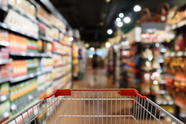 Shopping cart with supermarket aisle blur abstract background stock photo
