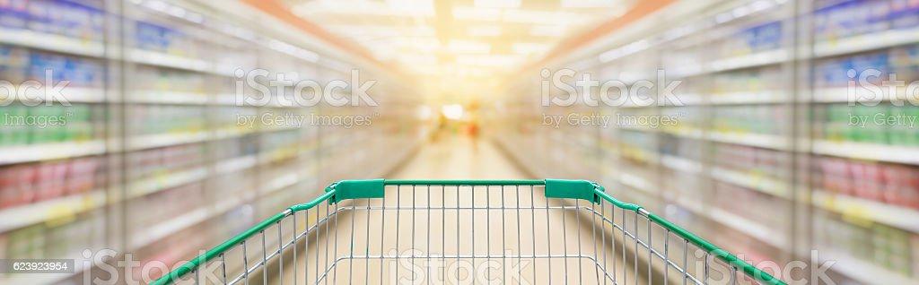 Shopping cart with supermarket aisle blur background stock photo