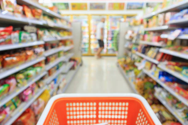 Shopping cart with Supermarket convenience store aisle shelves interior blur for background Shopping cart with Supermarket convenience store aisle shelves interior blur for background snack aisle stock pictures, royalty-free photos & images