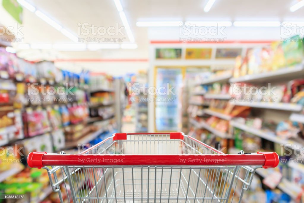 Shopping cart with Supermarket convenience store aisle shelves interior blur for background Shopping cart with Supermarket convenience store aisle shelves interior blur for background Abstract Stock Photo