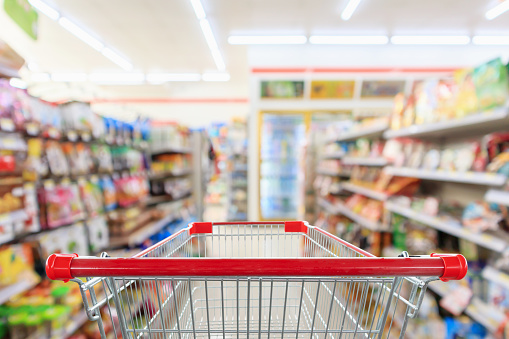Shopping Cart With Supermarket Convenience Store Aisle Shelves Interior Blur For Background Stock Photo - Download Image Now