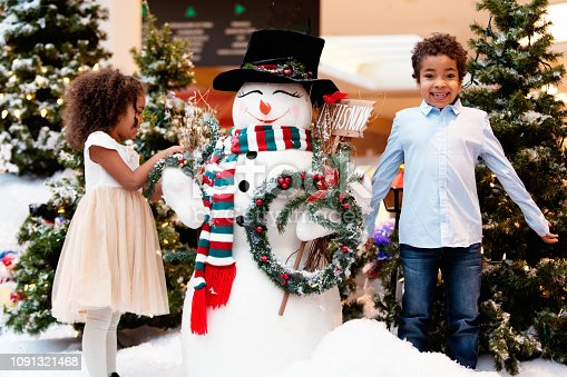 Multi-Ethnic family shops at Shopping Mall during Christmas Time with Santa Claus. Brother and sister are having fun with a snowman. Photo was taken in Quebec Canada.