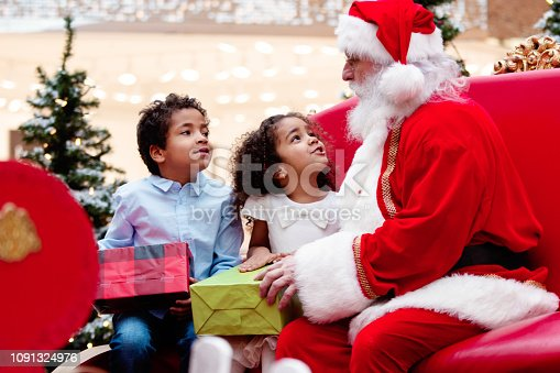 Multi-Ethnic family shops at Shopping Mall during Christmas Time with Santa Claus. Santa Claus is asking the children what they want for Christmas. Brother and sister tells Santa Claus what they want. Santa Claus has gifts in his hands and give them. Photo was taken in Quebec Canada.