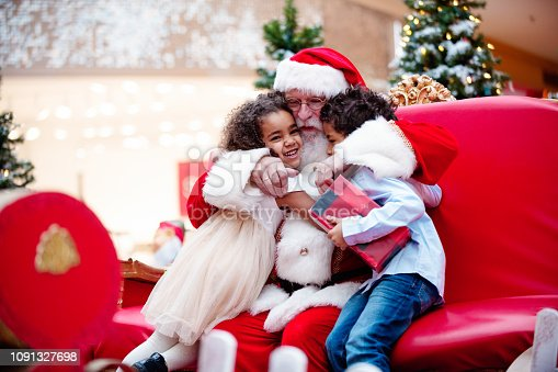 Multi-Ethnic family shops at Shopping Mall during Christmas Time with Santa Claus. Santa Claus is asking the children what they want for Christmas. Brother and sister happy to see Santa Claus. They are hugging. Santa has arms around children. Boy has gift in his hands. Photo was taken in Quebec Canada.
